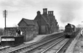 Asfordby station on the MR line from Syston to Melton Mowbray with Kettering-based Stanier 8F No.48069 at the head of a Down minerals on 9th February 1957.