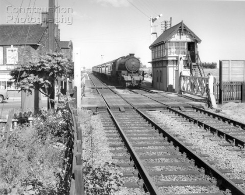 Thompson Class B1 at the head of a passenger train passes a signal box and level crossing at an unkn