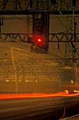 A dramatic night view of a speeding train and signal.