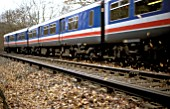 Autumn  leaves are stirred as a class 319 electric speeds past. C1993