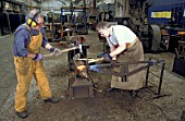 Workers carry out wrought ironwork in the forge at Wolverton Works. C1993