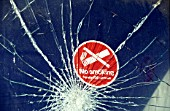 No Smoking sign on shattered window of vandalised railway carriage. C1993