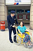 A helping hand for a disabled passenger at London, Waterloo station. C 1992