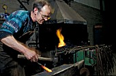 Blacksmith at work in the forge at Wolverton Works. C 1993