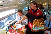 A Virgin Trains employee serves breakfast to a commuter onboard a London Euston bound Pendolino. 2004.